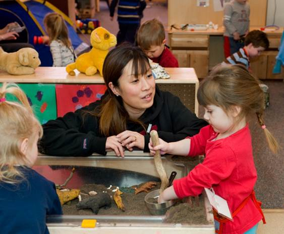 A teacher interacts with a child that is playing in a sandbox in the WSU Children's Center.